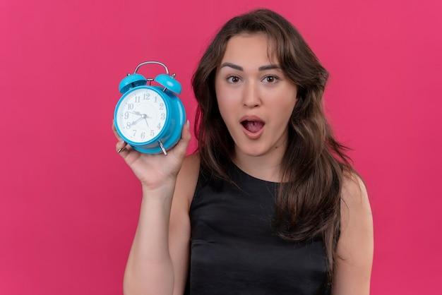 Surprised caucasian girl wearing black undershirt holding a alarm clock on pink background
