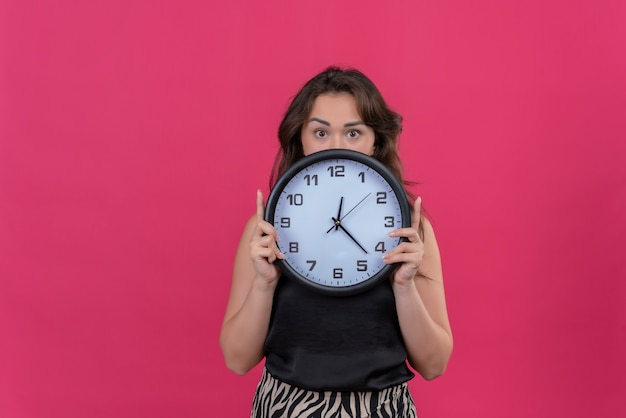 Surprised caucasian girl wearing black undershirt holding a wall clock on pink background