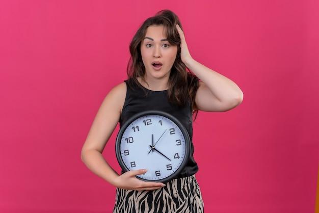 Ragazza caucasica sorpresa che porta maglietta nera che tiene un orologio da parete e mise la mano sulla testa su sfondo rosa