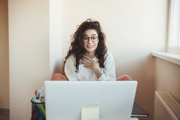 Удивленный кавказский студент в очках проводит онлайн-урок с ноутбуком