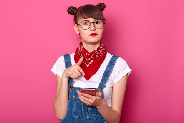 驚いた白人のティーンエイジャーの女の子は彼女のガジェットを手に持って、彼女のsmat電話で人差し指でポイントし、信じられない、ニュースに衝撃を与えた、ピンクの壁に立ち向かい、カメラを見ています。コピースペース。