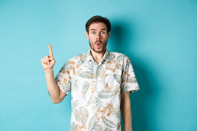 하와이안 셔츠에 놀란 백인 관광객, 손가락을 가리키고 와우, 승진을 확인하고 파란색 배경에 서 있습니다.