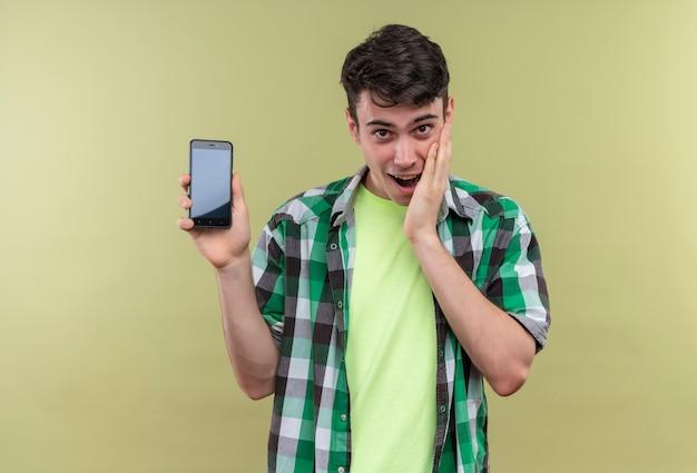 Удивленный кавказский молодой парень в зеленой рубашке с телефоном положил руку на щеку на изолированном зеленом фоне