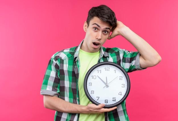 벽 시계를 들고 녹색 셔츠를 입고 놀란 백인 젊은 남자가 고립 된 분홍색 배경에 머리에 손을 넣어