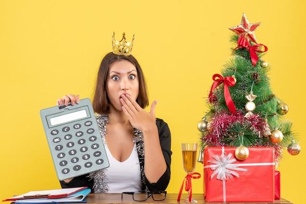 Signora affascinante sorpresa in vestito con il calcolatore della tenuta della corona nell'ufficio su colore giallo isolato