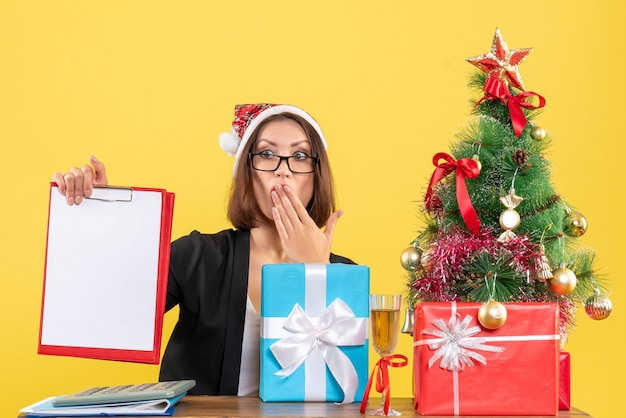 Surprised charming lady in suit with santa claus hat looking at document in the office on yellow isolated