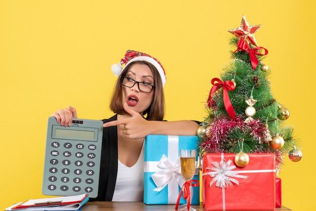 Signora affascinante sorpresa in vestito con il cappello di babbo natale che mostra calcolatrice nell'ufficio su colore giallo isolato