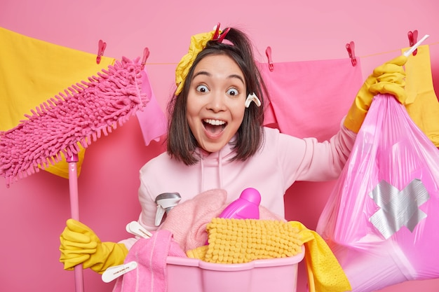 Surprised cheerful brunette asian woman keeps mouth opened carries trash bag and mop poses near laundry basket stands near clothesline against pink wall