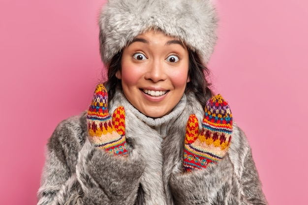 Surprised cheerful eskimo girl stares at front smiles broadly raises hands dressed in traditional grey fur coat and hat isolated over pink wall