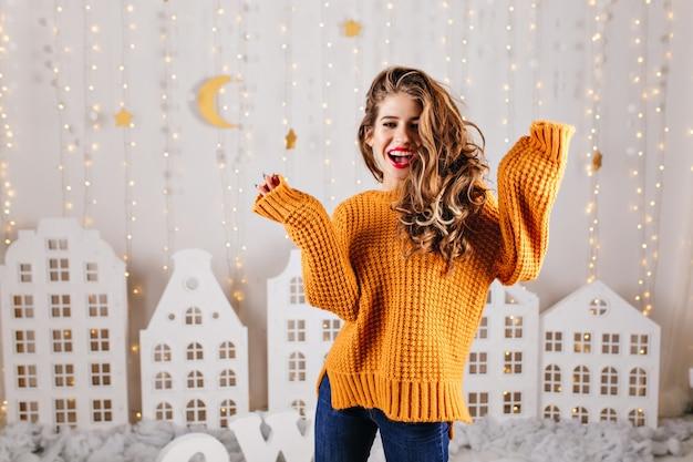 놀랍고 쾌활한 소녀가 아늑한 새해 분위기에서 행복하게 웃으며 니트 스웨터 오버 사이즈로 초상화 포즈를 취합니다.
