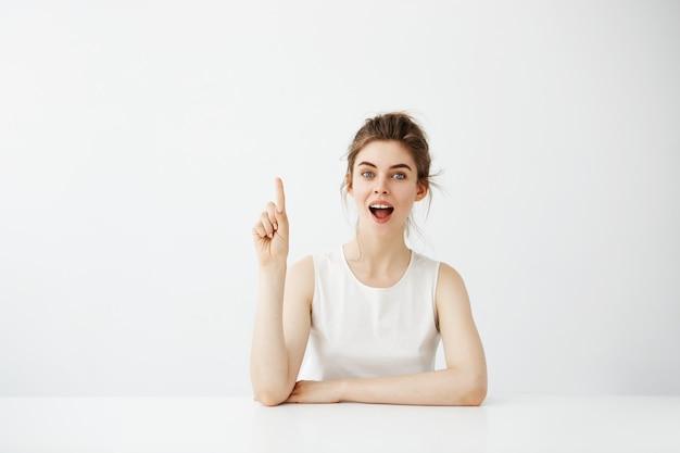 Удивленная жизнерадостная милая женщина с раскрытым ртом указывая палец вверх сидя на таблице над белой предпосылкой.