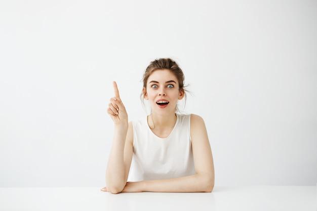 白い背景の上のテーブルに座って口を開いた人差し指で驚いて陽気なきれいな女性。