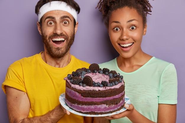 놀란 쾌활한 여자와 남자는 접시에 큰 맛있는 케이크를 보유하고 생일 친구를 축하합니다