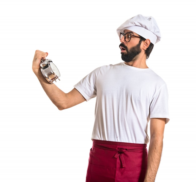 Sorpreso chef in possesso di un orologio su sfondo bianco