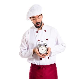 Chef sorpreso che tiene un orologio su sfondo bianco