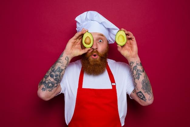 수염과 빨간 앞치마를 가진 놀란 요리사가 아보카도를 들고 있습니다.