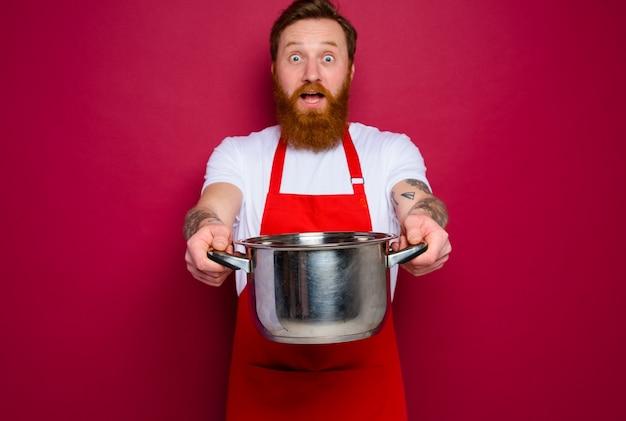 수염과 빨간 앞치마가있는 놀란 요리사가 요리 할 준비가되었습니다.