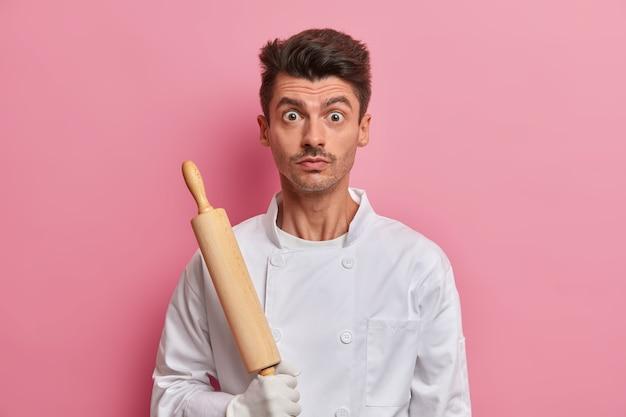 白い制服を着た、キッチンツールを持った驚いたシェフ、忙しいパン屋がめん棒を持っています
