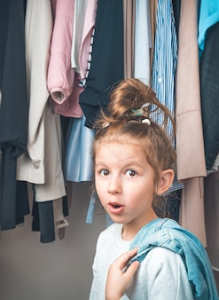 Surprised child on the background of things hanging on a hanger. side view.