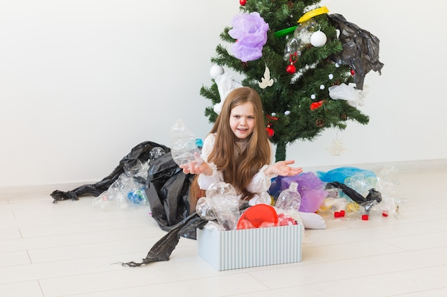 Surprised child carrier box with plastic trash over christmas tree