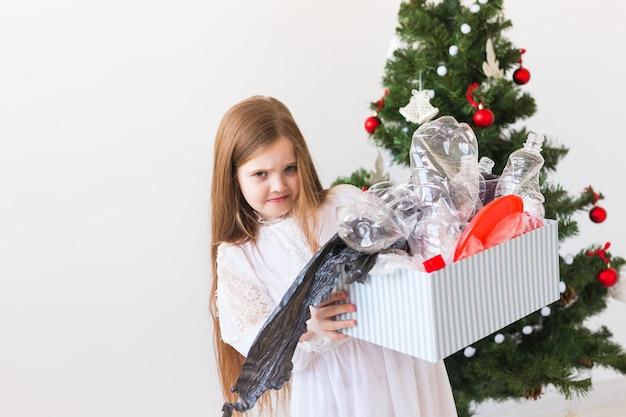 Удивленная детская переноска с пластиковым мусором над елкой