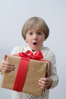 Surprised child holding christmas gift box in hand. boy on white background. new year and x-mas concept.