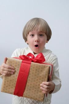 クリスマスのギフトボックスを手に持って驚いた子供。白い背景の上の少年。新年とクリスマスのコンセプト。