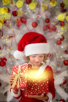 驚いた子供が魔法のクリスマスギフトボックスを開きます。クリスマスの休日の概念