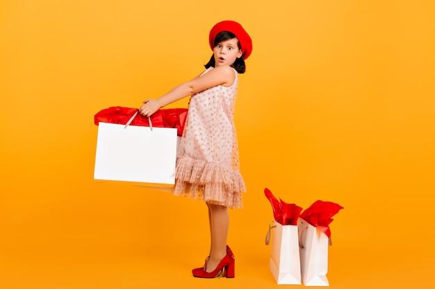 母の靴でポーズをとって驚いた子供。黄色の壁に買い物袋を持っている驚いたプレティーンの女の子。