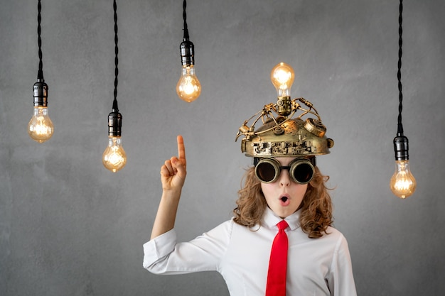 회색 벽에 전구와 놀된 아이입니다. 밝은 새로운 아이디어 개념
