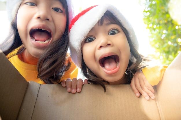 Удивленные дети распаковывают рождественскую подарочную коробку