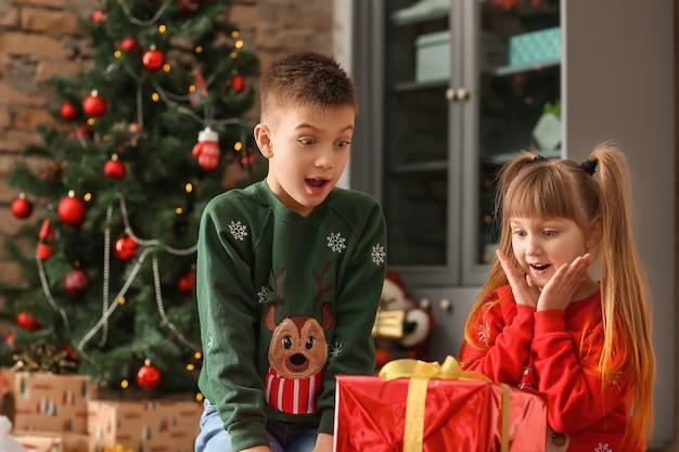 自宅でクリスマスプレゼントを持って驚いた子供たち