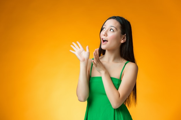 The surprised chinese girl on yellow background