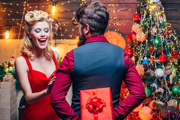 놀란 된 크리스마스 커플입니다. 흥분되고 행복합니다. 입 열기, 감정. 크리스마스 겨울 커플 오프닝