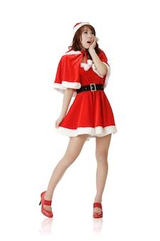 驚いたクリスマスの女の子、白い壁に分離された全身像。