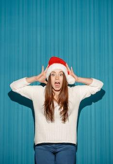 블루 스튜디오 배경에 산타 모자를 쓰고 놀란 크리스마스 소녀