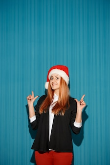 青いスタジオの背景にサンタの帽子をかぶって驚いたクリスマスの女の子