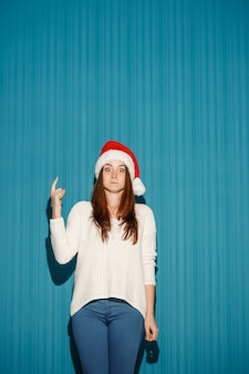 Surprised christmas girl wearing a santa hat pointing up on the blue studio background