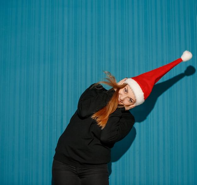 サンタの帽子をかぶって驚いたクリスマス女性