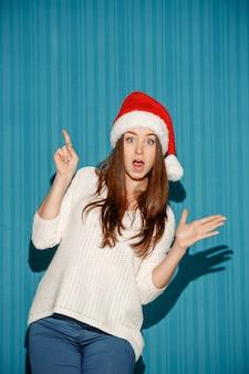 Удивленная женщина в новогодней шапке