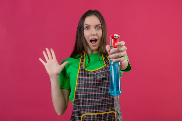 孤立したピンクの背景に手を上げるクリーニングスプレーを保持している手袋で制服を着て驚いたクリーニングの若い女の子
