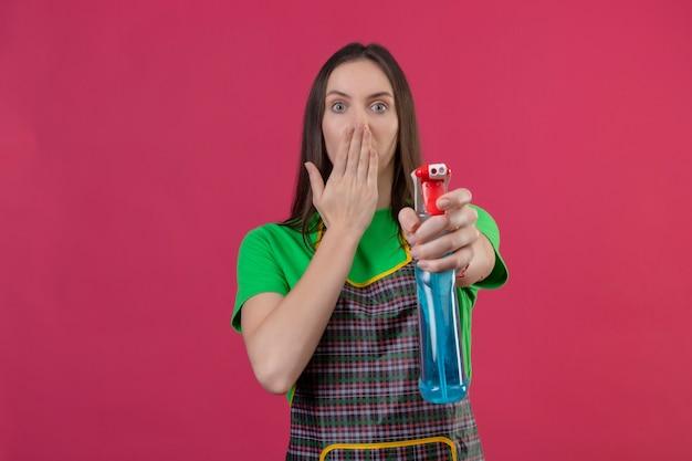 孤立したピンクの背景にカメラで覆われた口にクリーニングスプレーを差し出す手袋で制服を着て驚いたクリーニングの若い女の子