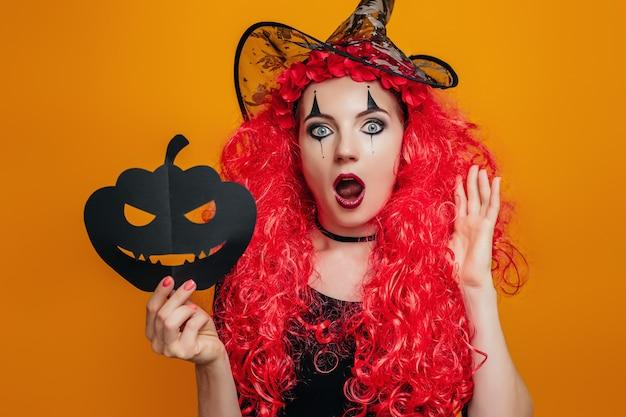 Удивленная девушка-клоун в костюме на хэллоуин держит бумажную тыкву и кричит