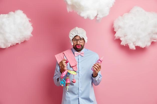 Удивленный невежественный бородатый мужчина готовится стать отцом, держит бутылочку для кормления, а мобильная игрушка сосет соску, носит подгузник на голове, собирает предметы для роддома, позирует у розовой стены
