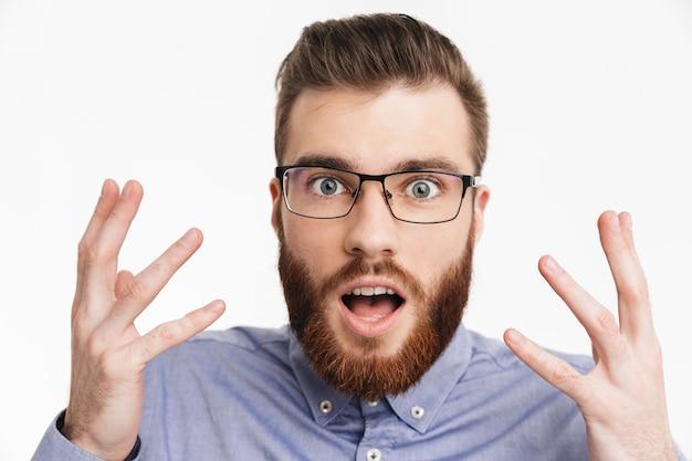 Удивленный сбитый с толку бородатый элегантный мужчина в очках смотрит