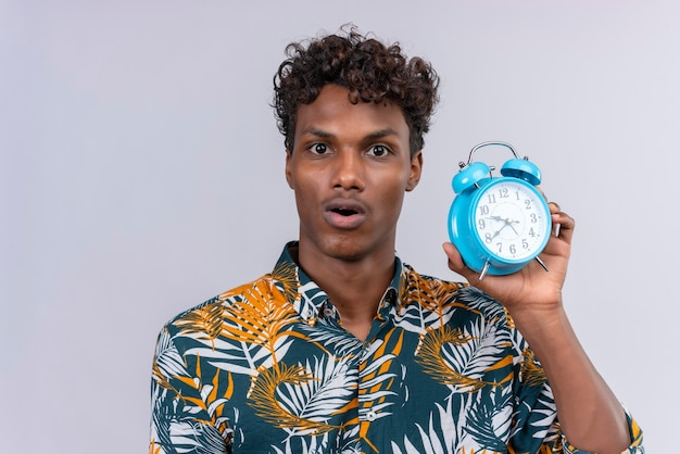 Surprised and confused young handsome dark-skinned man with curly hair in leaves printed shirt holding blue alarm clock on a white background