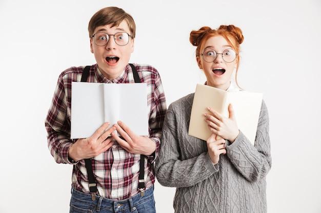 本を持っている学校のオタクの驚いたカップル