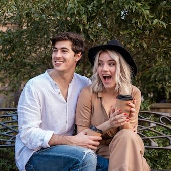 Удивленная пара на скамейке с чашкой кофе