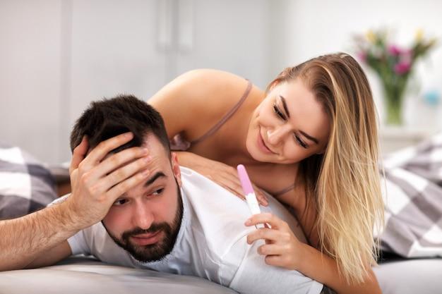침실에서 임신 테스트와 놀란 된 부부