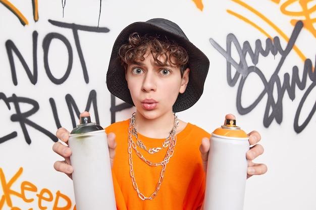 Surprised creeative teenage boy disrupts street walls holds two aerosol sprays makes graffiti has wondered expression